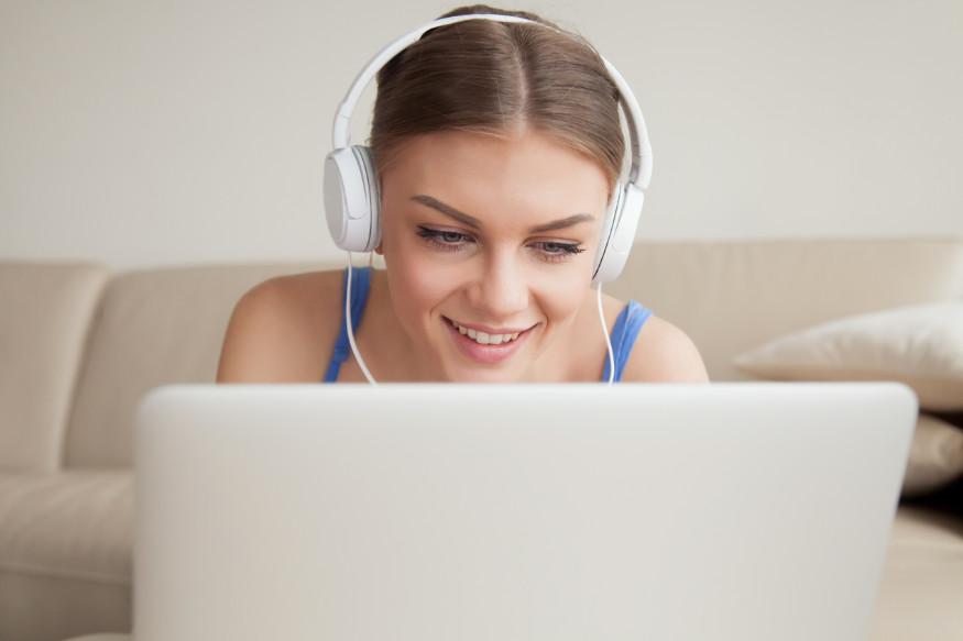kobieta ze słuchawkami przed komputerem